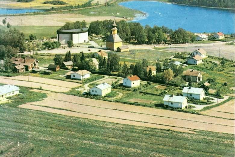 Vanhaa Oriveden kirkonkylää 1960-luvun jälkeen, Kaarikirkko ja kellotapuli taka-alalla, edessä peltoa ja asuin- ja liiketaloja.