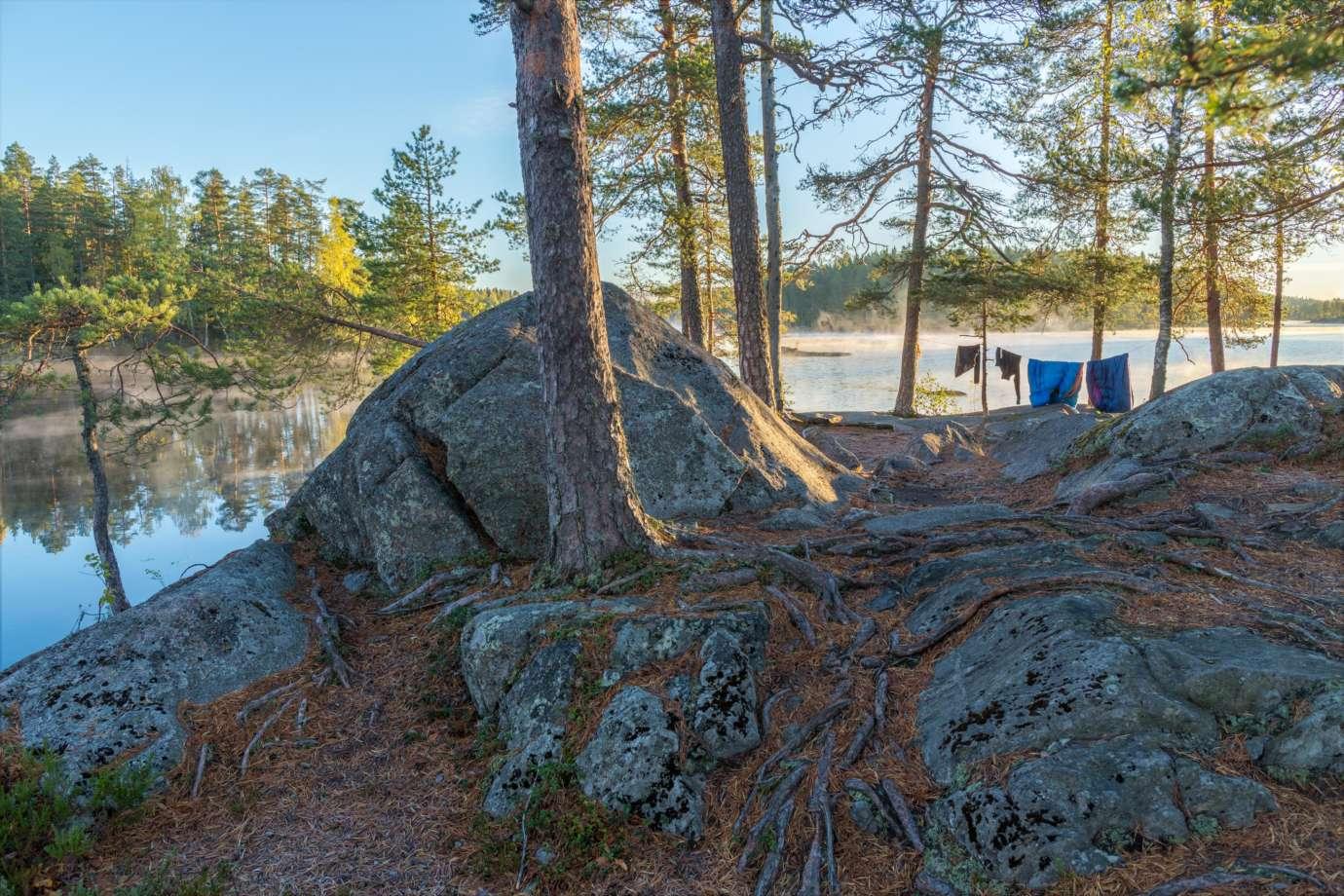 Pukalan virkistysmetsän kallioista järvenrantaa ja uimapussit kuivumassa narulla aamuisessa sumussa alkusyksyn auringossa.