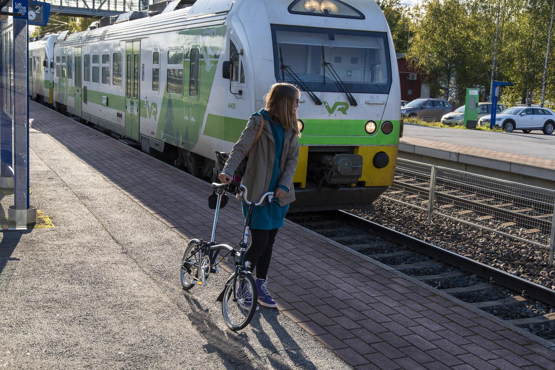 Nainen odottaa Oriveden asemalla junaa taittopyöränsä kanssa. Hän on matkalla Tampereelle.