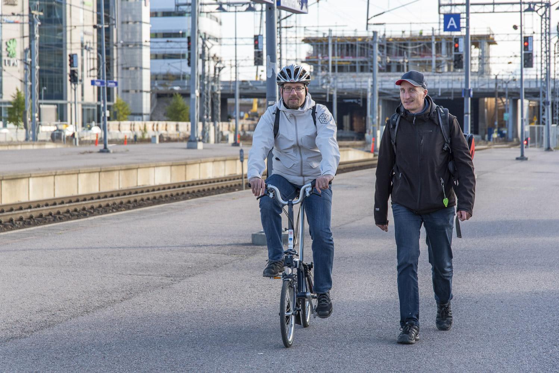 Kaksi miestä. Toinen miehistä pyöräilee ja toinen kävelee vieressä. Miehet juttelevat. Kävely ja pyöräily.