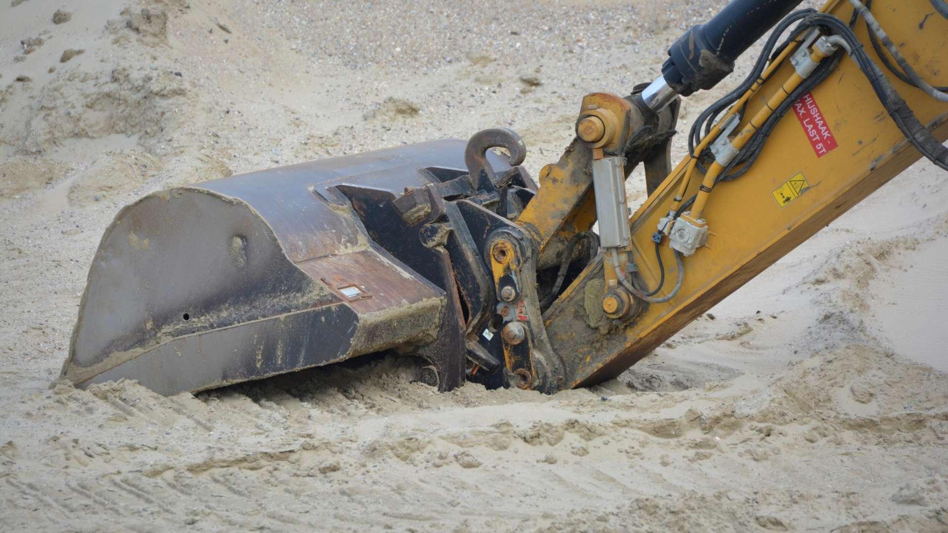 Kaivinkoneen kauha kaivaa hiekkaista maata. Muuta osaa kaivinkoneesta ei näy.