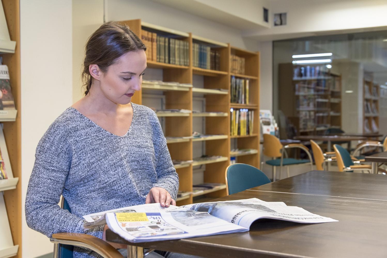 Asiakas lukee lehteä kirjaston lukusalissa