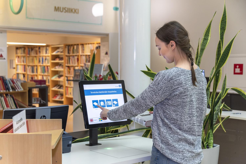 Kuvassa asiakas lainaa kirjaa lainausautomaatilla