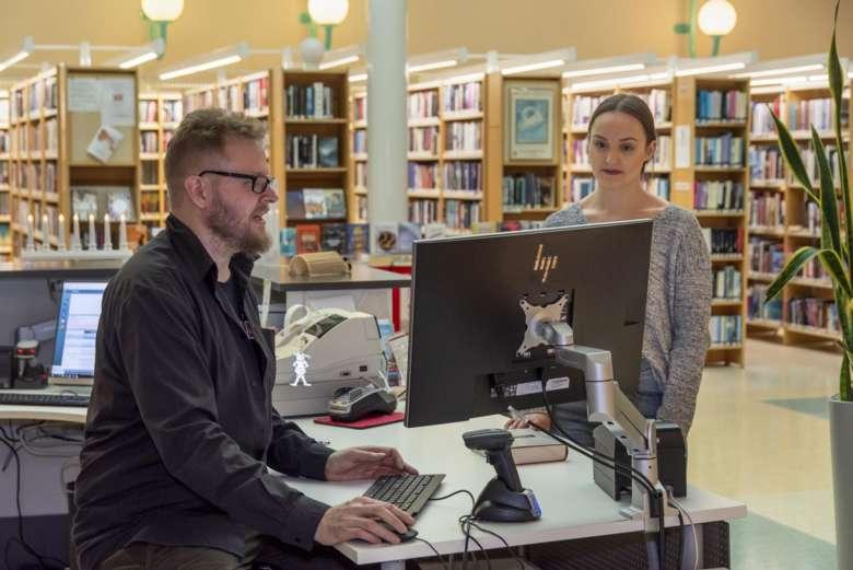 Kuvassa asiakas ja kirjastonhoitaja keskustelevat asiakaspalvelutiskillä
