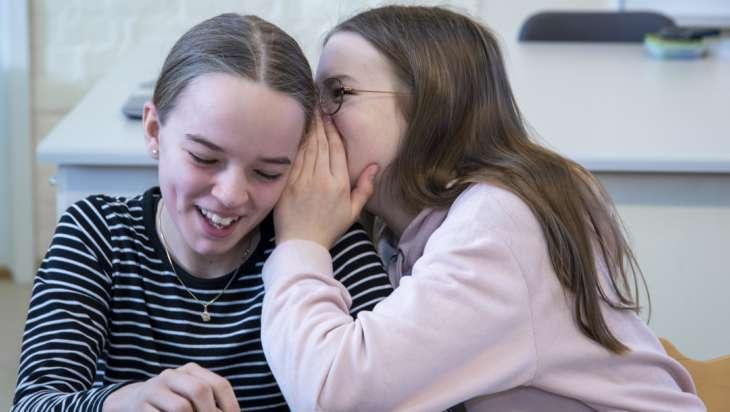 Kaksi koulutyttöä, joista toinen kuiskaa toiselle jotain kivaa.