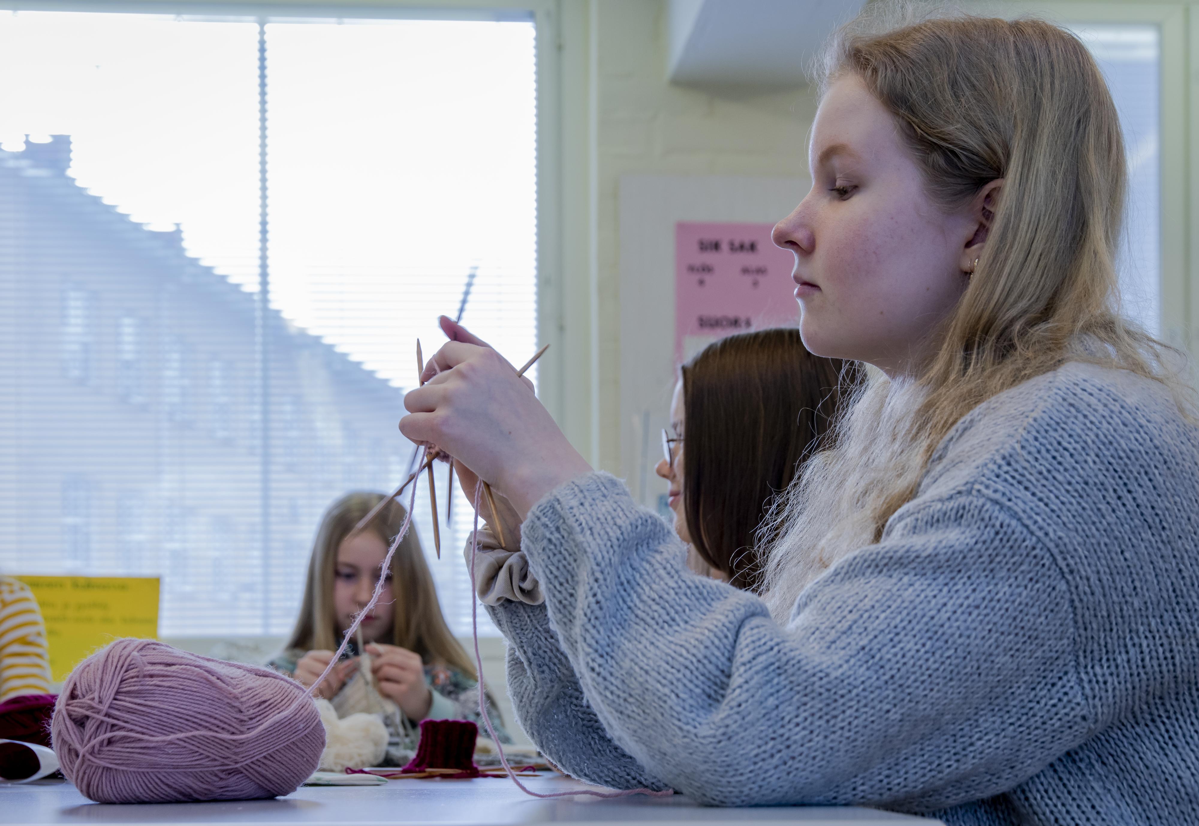 Kultavuoren koulun oppilas neuloo käsityötunnilla villasukkaa.