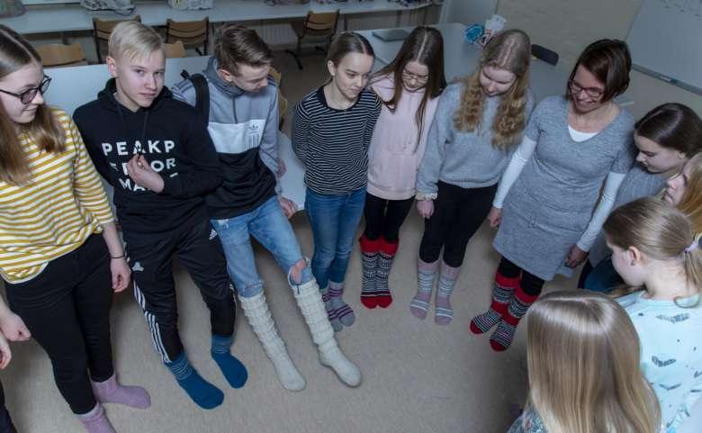 Kultavuoren koulun oppilaat ja opettaja esittelevät villasukkiaan.