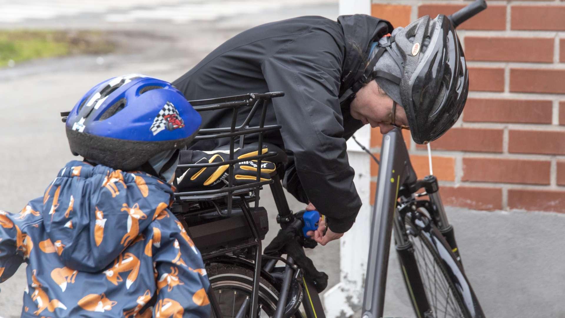 Nainen lukitsee polkupyörää. Naisen vieressä on pikkulapsi. Molemmilla on pyöräilykypärät. Liikenneturvallisuus on otettu huomioon