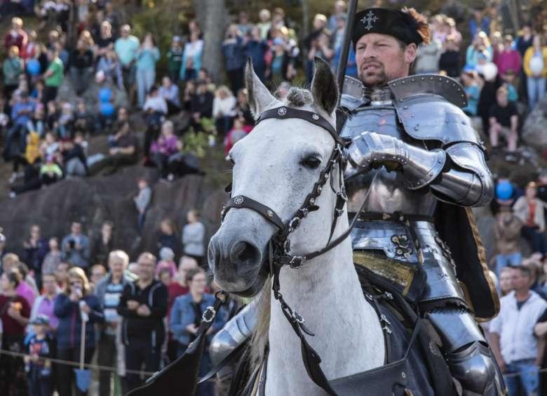 Haarniskoitu ritari valkoisen hevosen selässä Oriveden jäähallin yläkentällä, taustalla yleisöä istumassa Paltanmäen rinteellä.