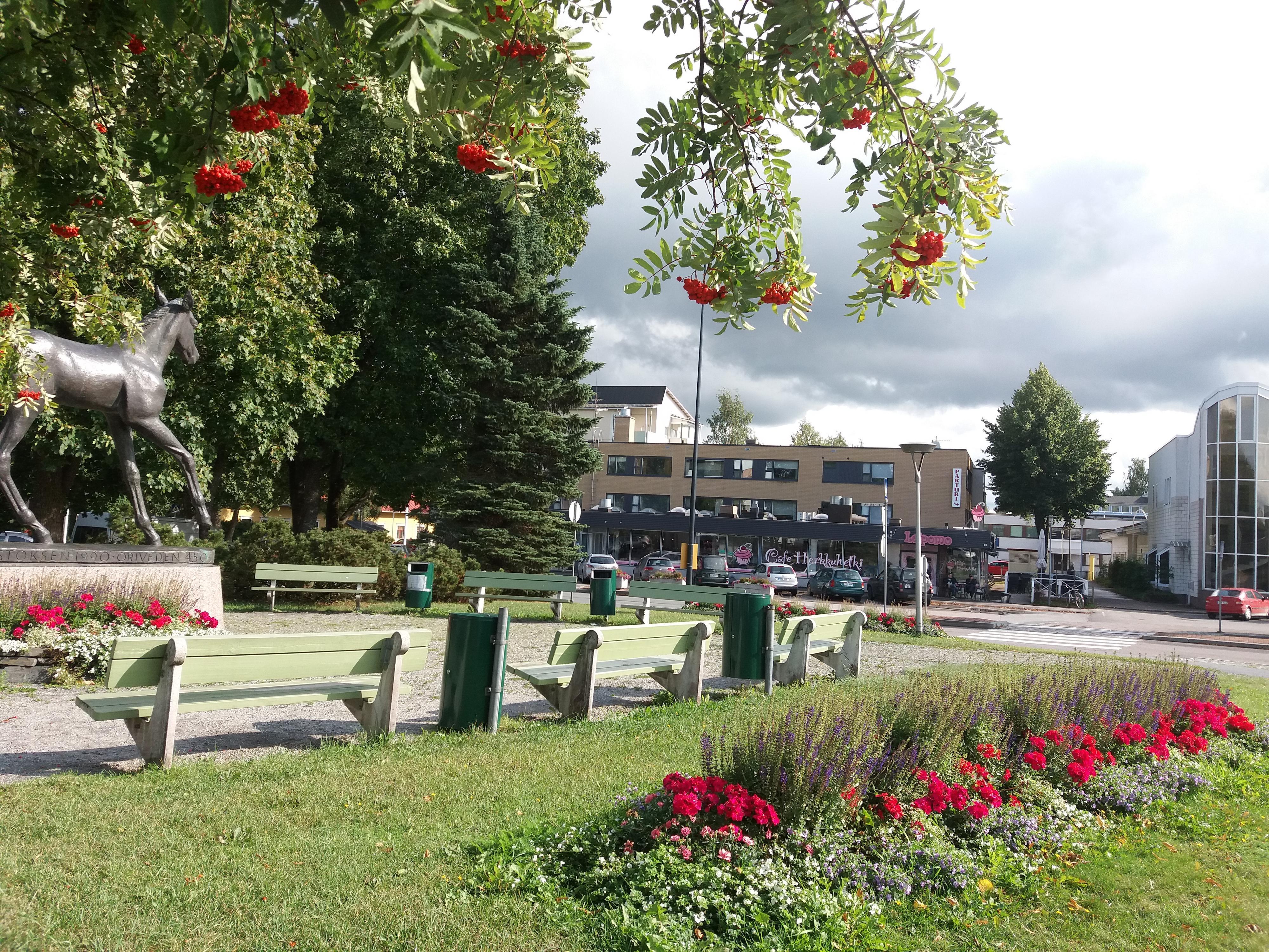 Oriveden keskustaa ja Orivarsa-patsaan puisto. Taustalla näkyy Cafe Herkkuhetki ja Osuuspankki.