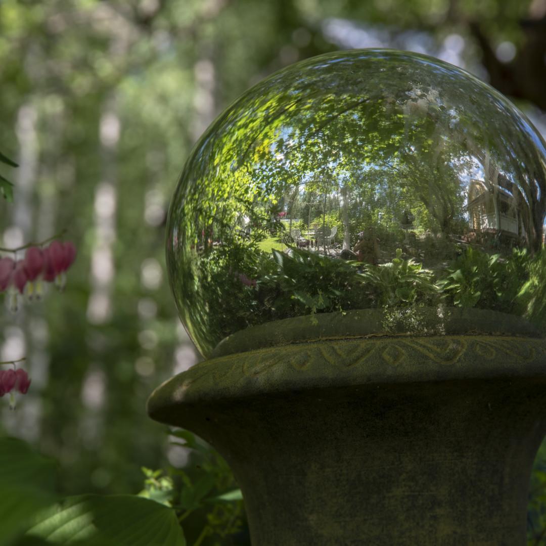 Käpälämäen pihaa. kuvassa lasipallo-pihakoriste, josta heijastuu ympäröivää vehreää vanhaa puutarhaa.