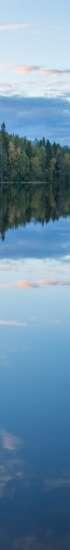 Pukala-järvi kesällä. Järvi on tyyni ja pilvet heijastuvat taivaalta järven pintaan.