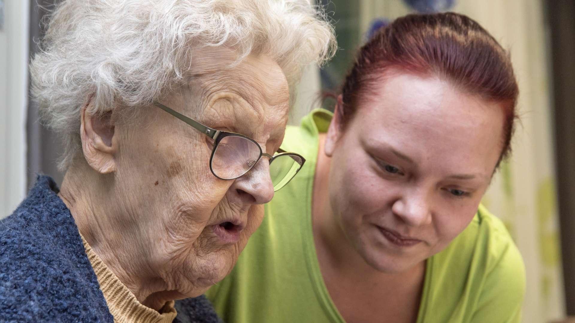 Iäkäs nainen ja nuorempi nainen tutkivat yhdessä jotakin.