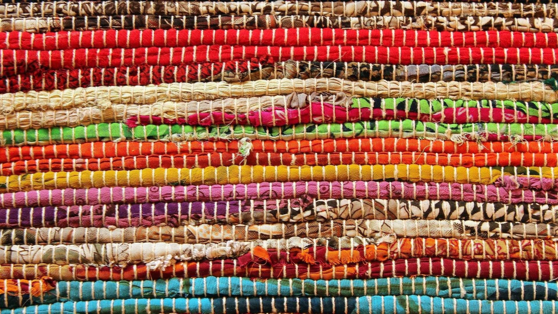 Värikäs raidallinen räsymatto. Matossa on monenvärisiä raitoja muun muassa sinistä, punaista ja keltaista.