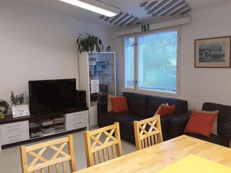 Järjestöjen talo olohuone, jossa on sohva- ja pöytäryhmiä sekä televisio.