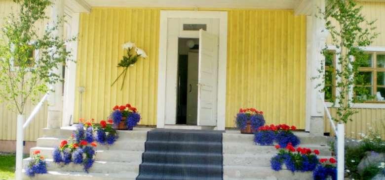 Leväslahden Pienviljelijäyhdistyksen talon rappuset on koristeltu juhlia varten kukkasin.