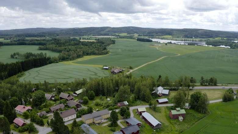 Orivesiläisessä maalaismaisemassa näkyy maatilan rakennuksia ja peltoja.