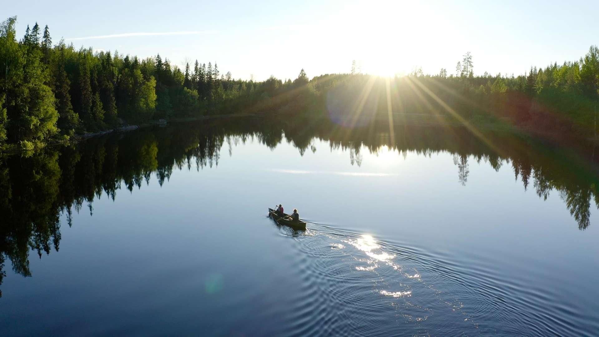 Kaksi ihmistä meloo tyynellä järvellä ilta-auringossa.