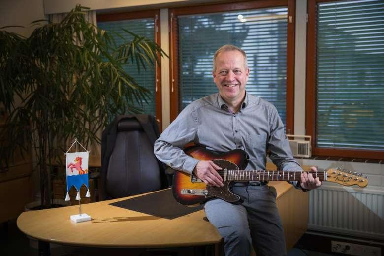 Kaupunginjohtaja istuu työhuoneessaan kitara kädessään ja Orivesi-viiri vierellään pöydällä.