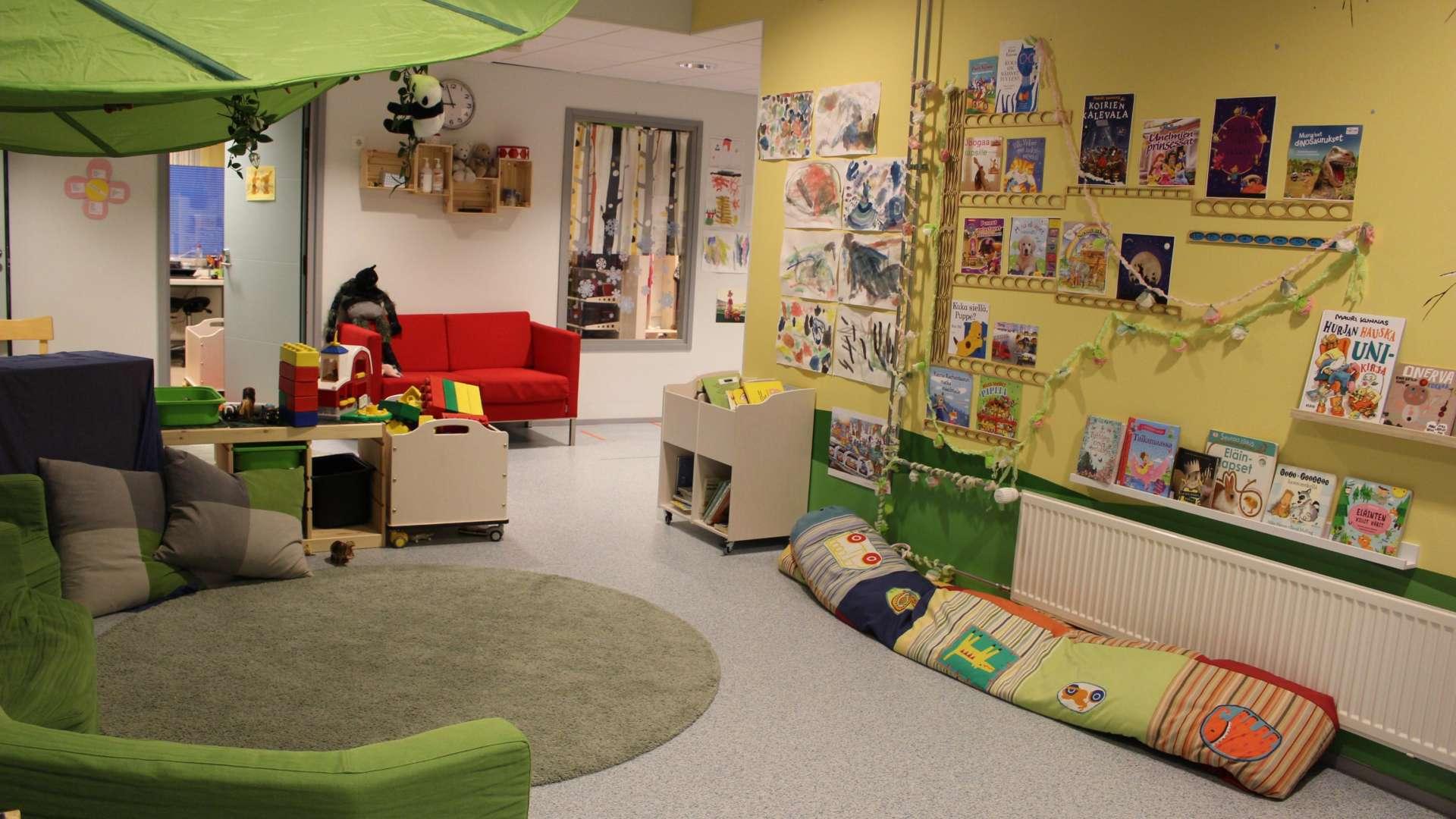 Päiväkodin huone, jossa muun muassa piirustuksia seinällä ja kirjoja hyllyssä ja leikkikaluja. Huoneessa on punainen sohva ja tyynyjä lattialla.