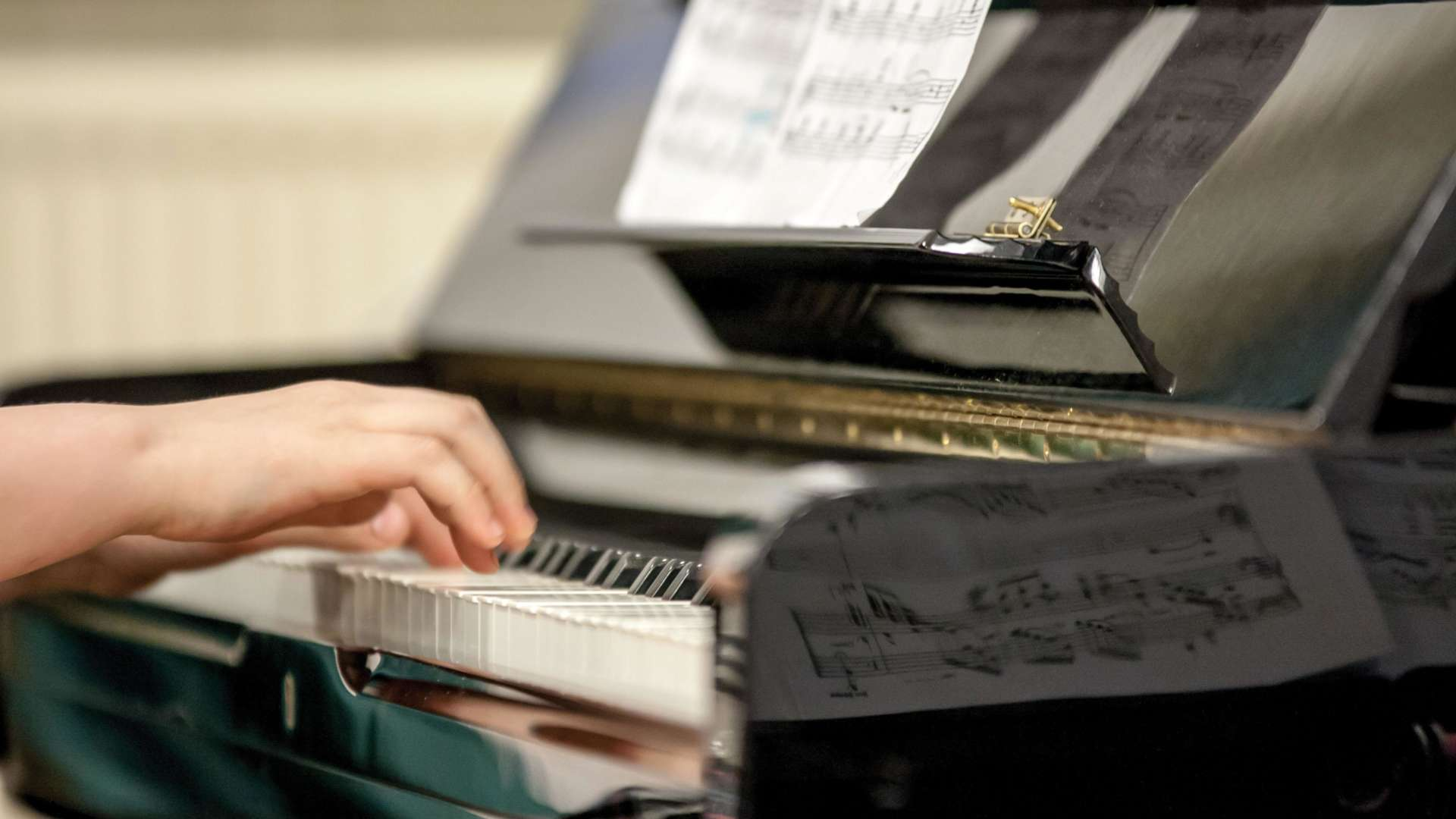 Pianistin kädet pianon koskettimilla.