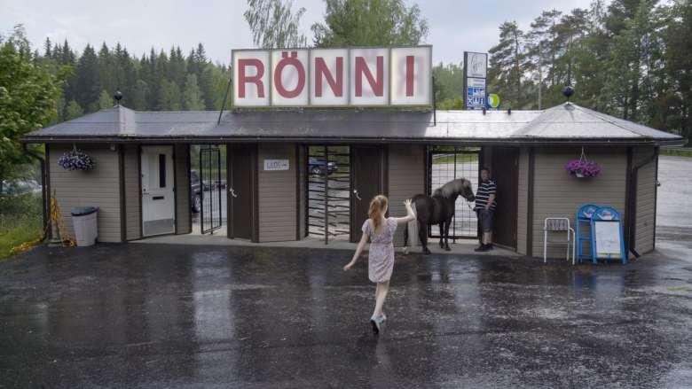 Rönnin portti, jonka alla ovat sadetta pitelemässä Kid-poni ja omistaja. Etualalla ponin hoitajatyttö.