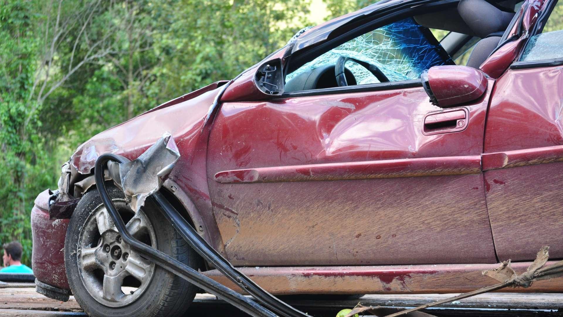 Punainen romuauto. Romuautosta näkyy vain etuosa. Ikkunat ovat rikki ja etuovi ja kylki ovat lommolla. Romuajoneuvo on alaosastaan ruosteinen/likainen.