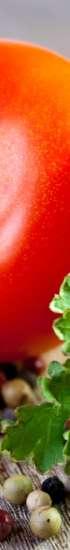 Punainen tomaatti, vihreätä salaattia ja erivärisiä pippureita pöydällä. Pippureita on mustia, punaisia ja valkoisia.