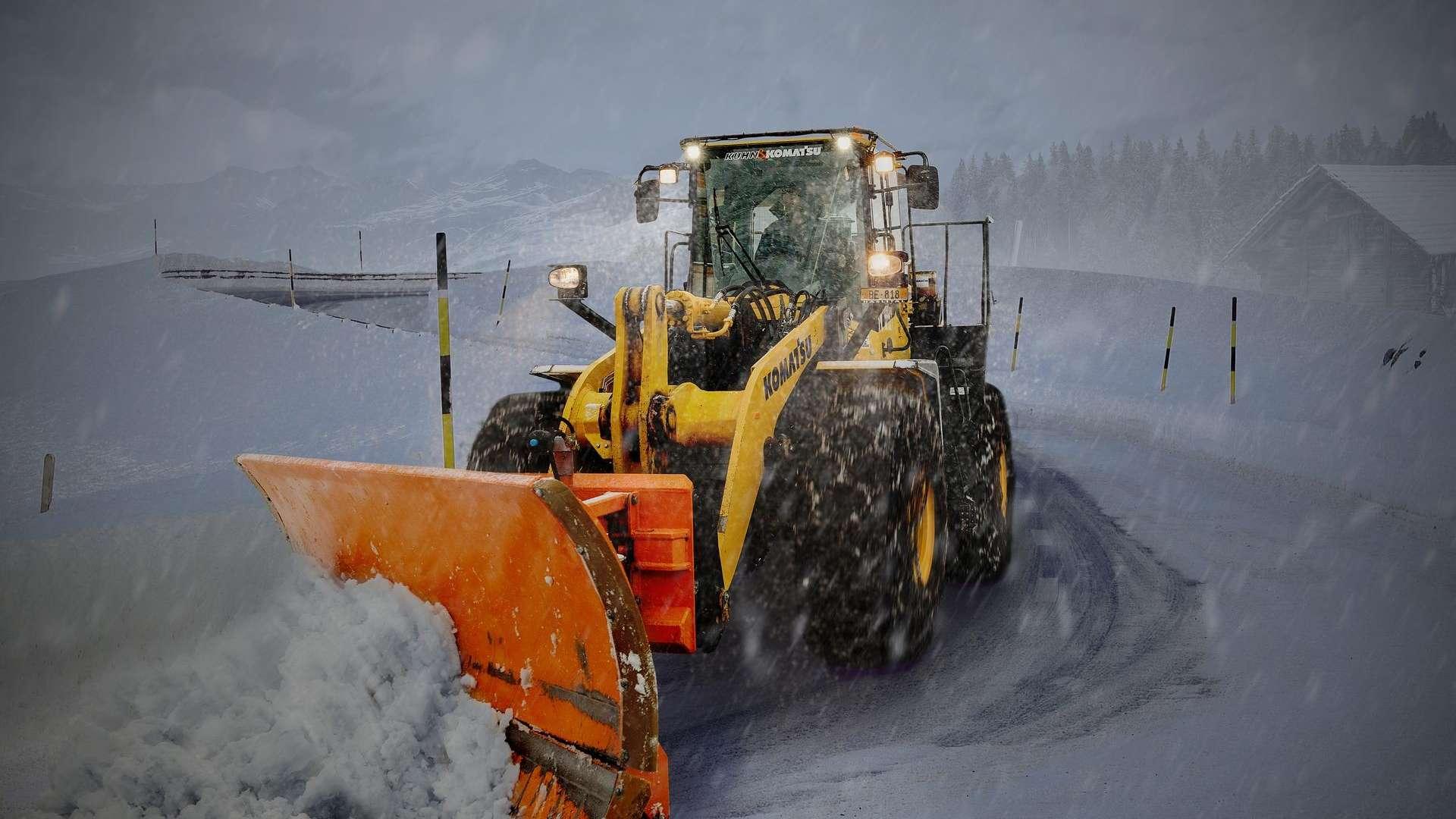 Keltainen traktori auraa tiellä lunta. On hämärää. Traktorissa on valot.