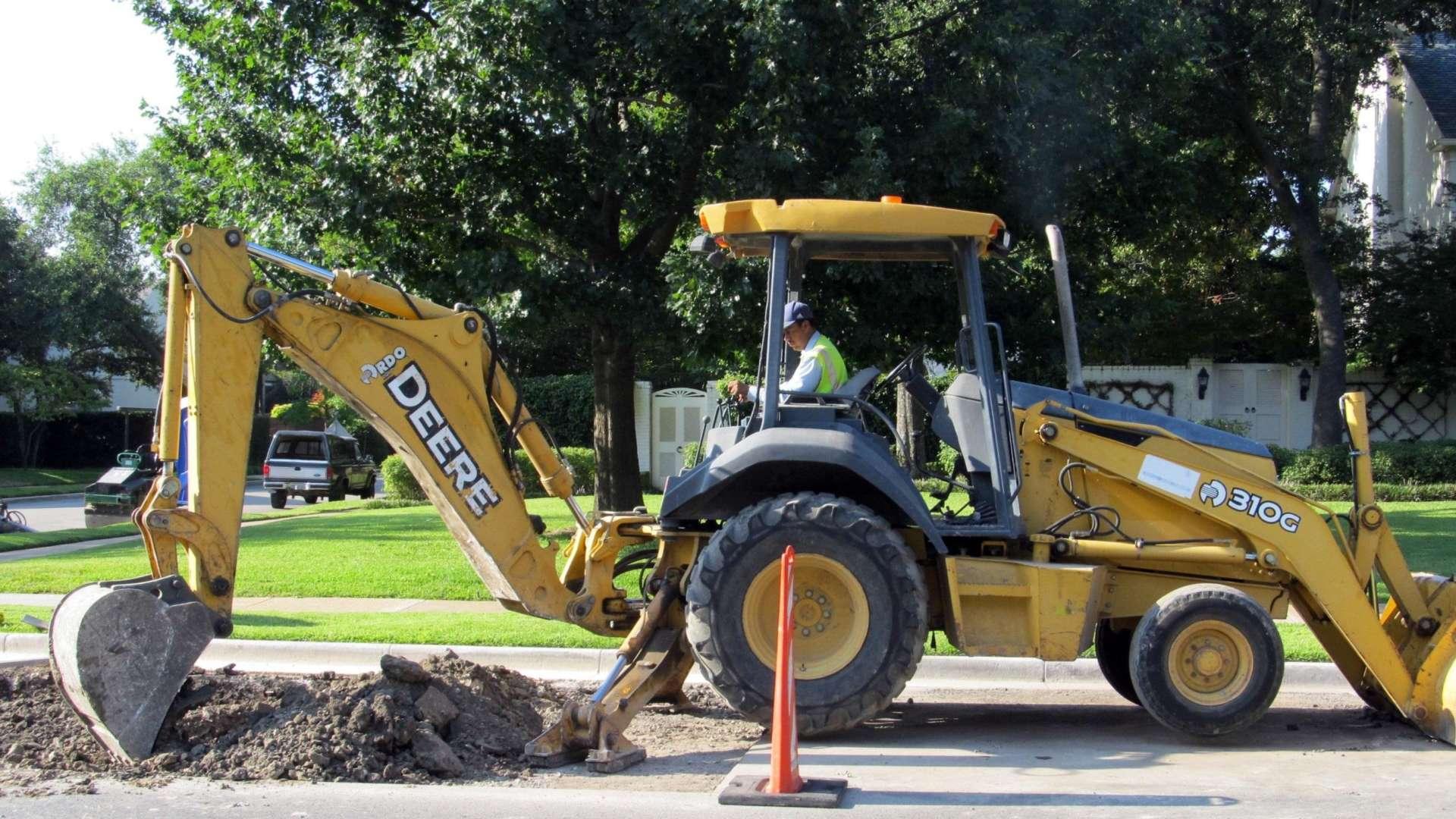 Keltainen traktorikaivin kaivaa asfalttia kadulla. On kesäpäivä.