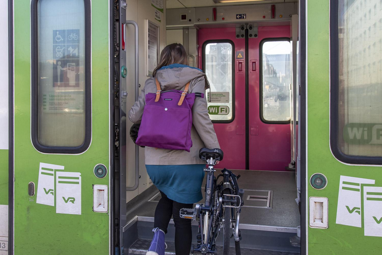 Nainen nousee junaan taittopyöränsä kanssa Oriveden asemalla.