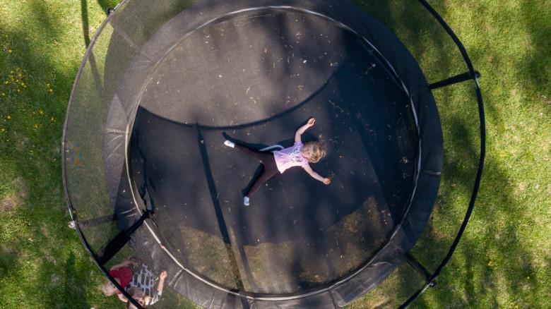 Tyttö makaa keskellä jättitrampoliinia, kuva otettu ilmasta.
