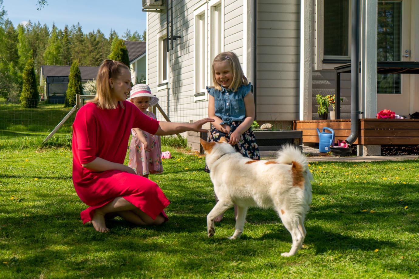 Perhe ja koira omakotitalon pihalla.