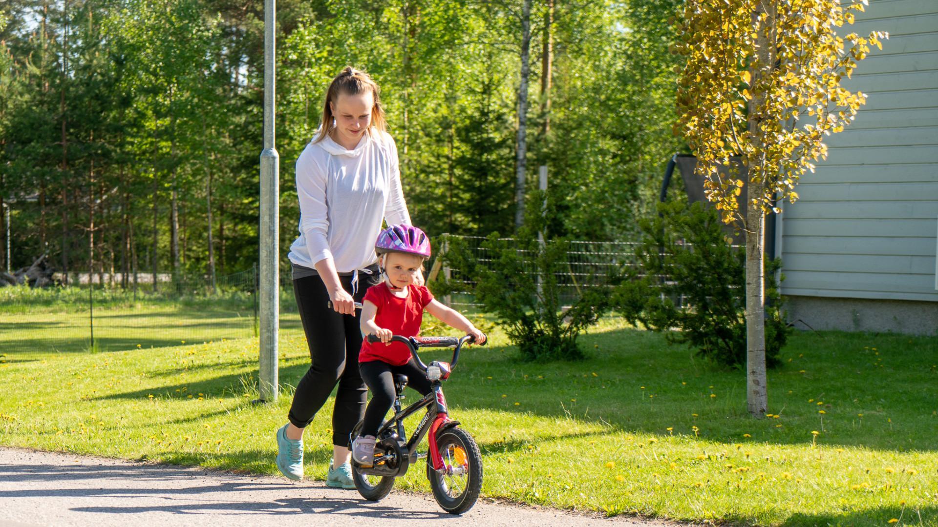 Äiti pyöräilyttää lasta kadulla.