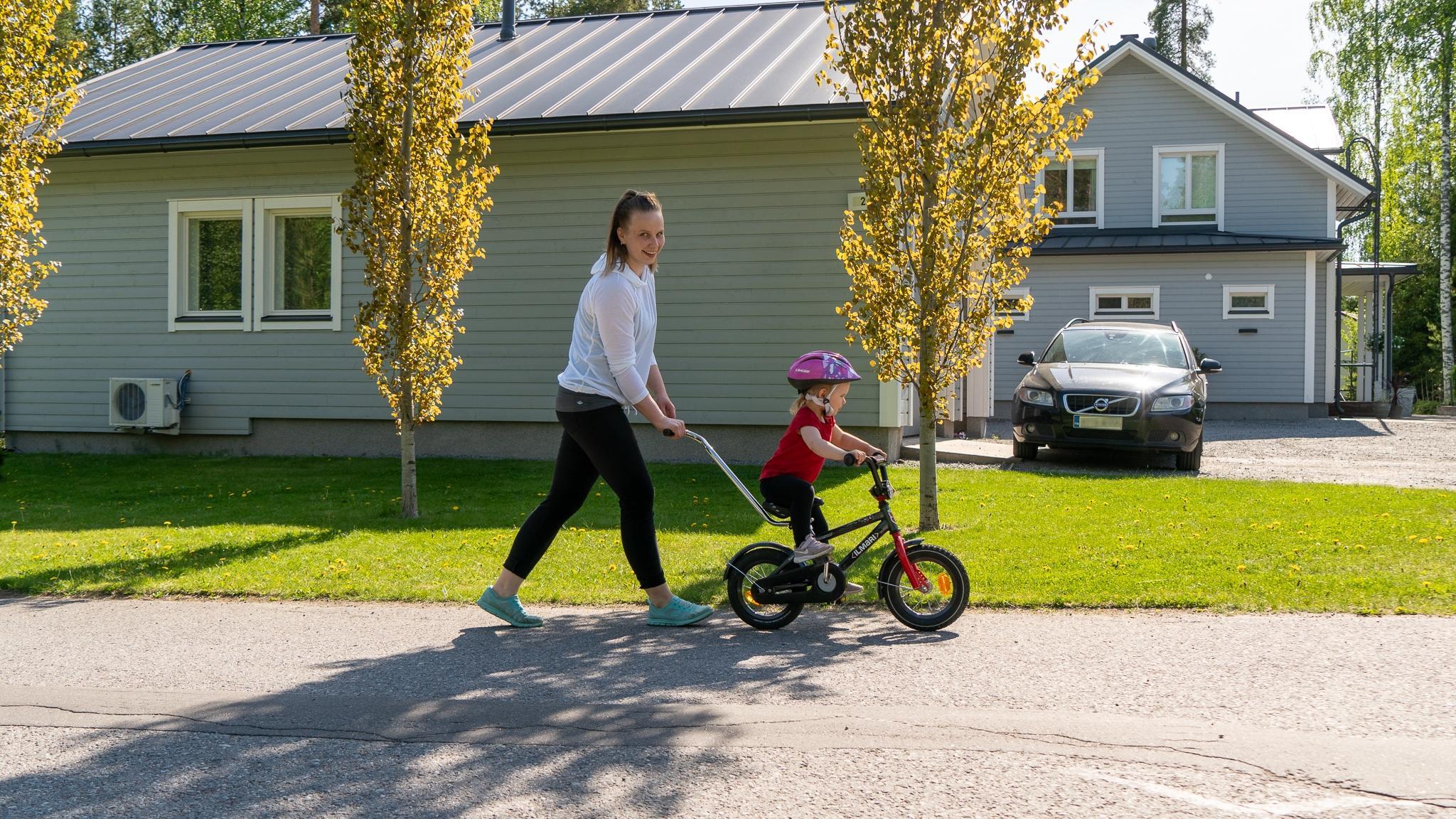 Äiti pyöräilyttää pikkutyttöä perheen omakotitalon edustalla.