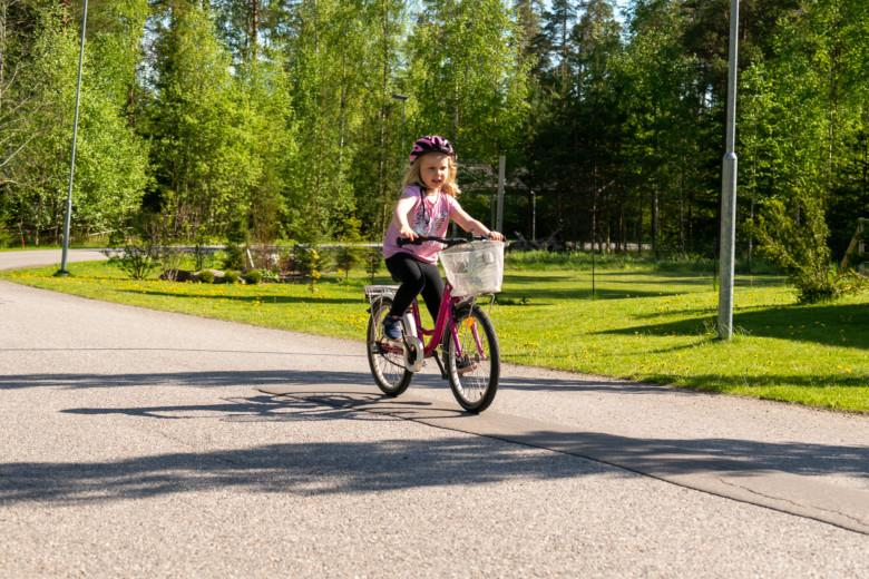 Tyttö pyöräilee kadulla.