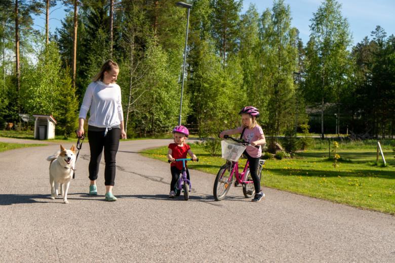 Kaisa, kaksi tytärtä ja koira lenkillä pihakadullaan Rovastinkankaalla.