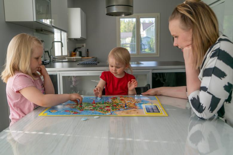 Äiti ja pikkutytöt pelaavat Afrikan tähti -peliä kotinsa keittiössä.