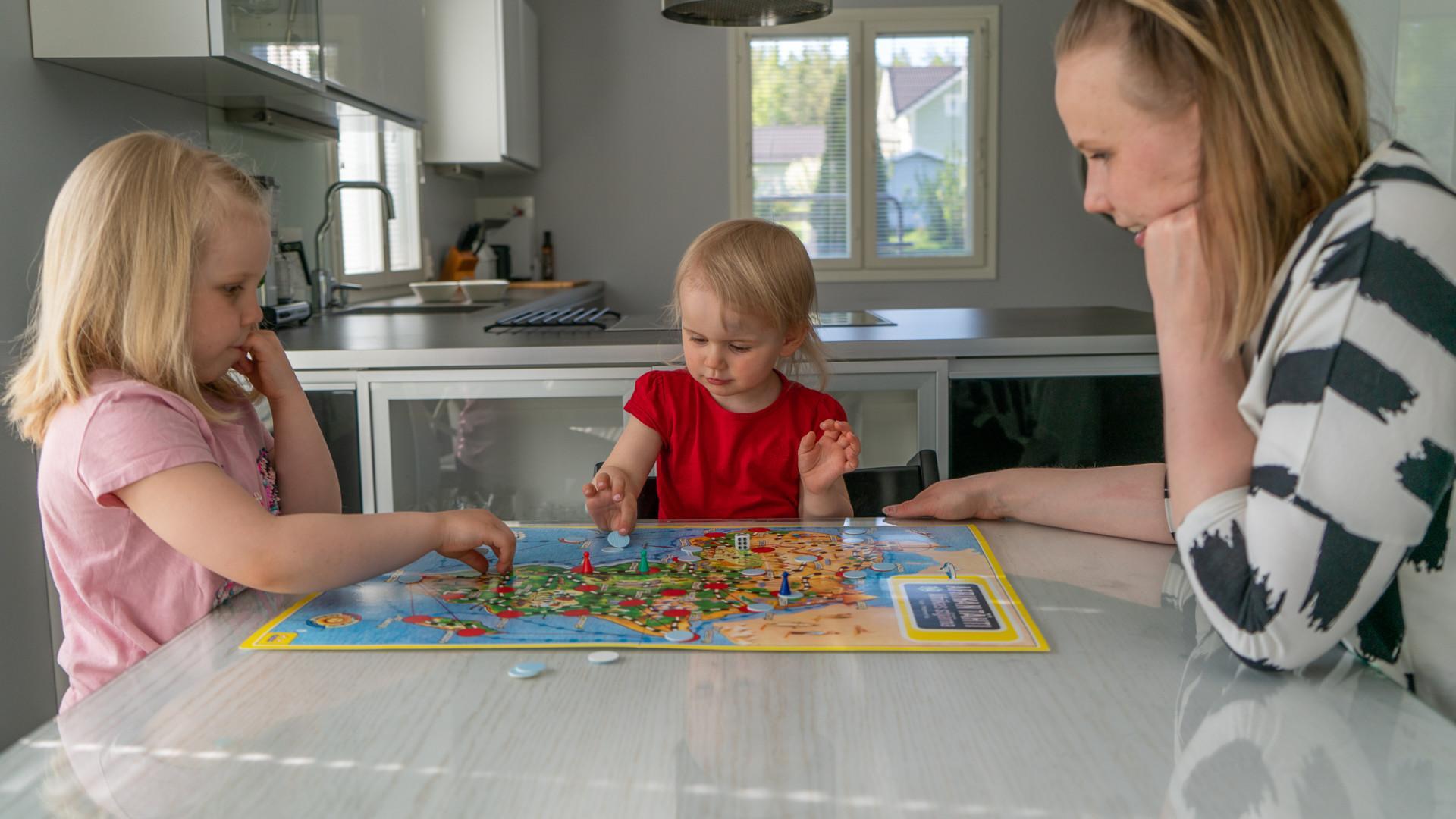 Äiti ja lapset pelaavat lautapeliä keittiössä.