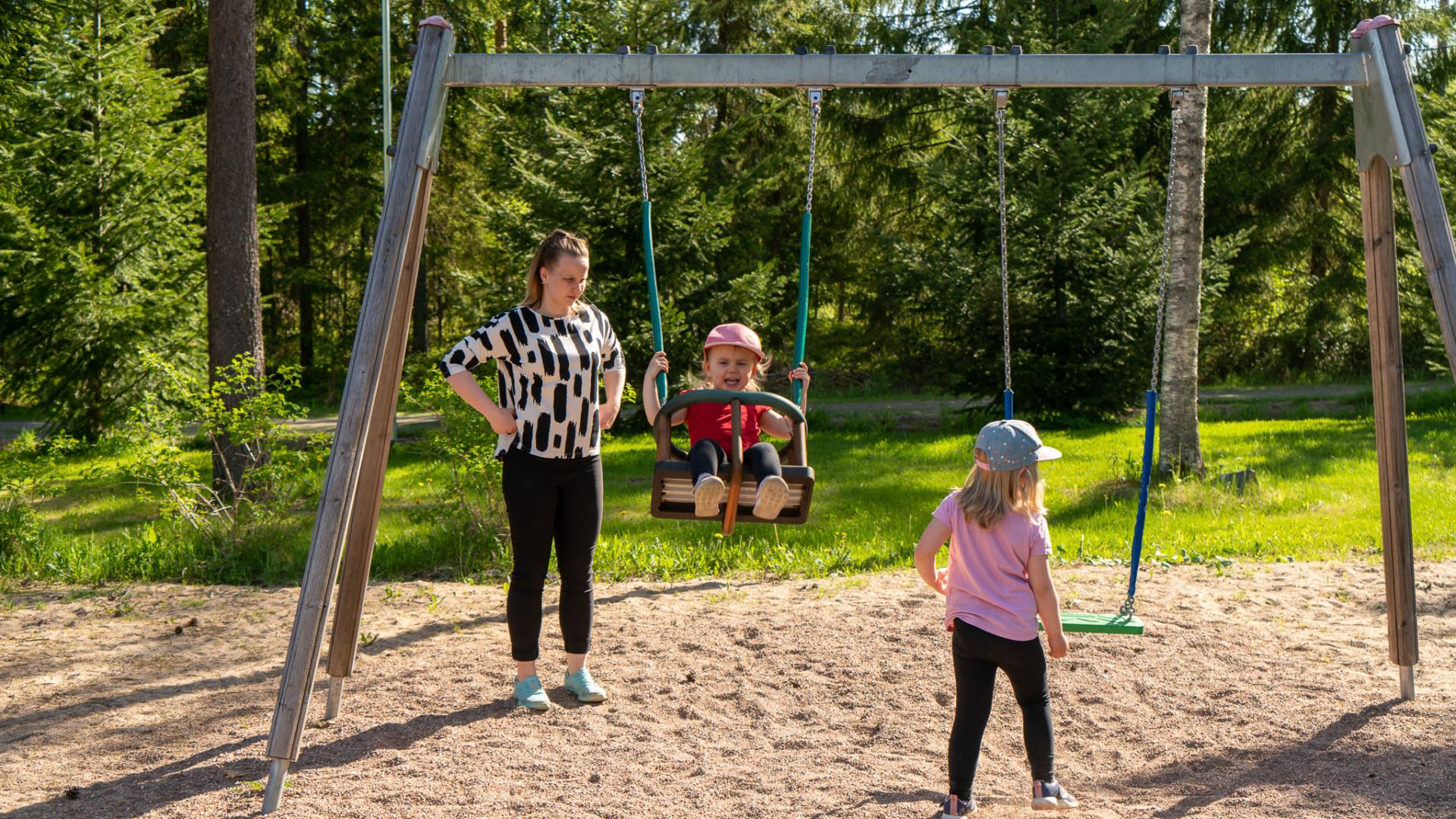 Äiti ja kaksi pikkutyttöä leikkipuistossa.