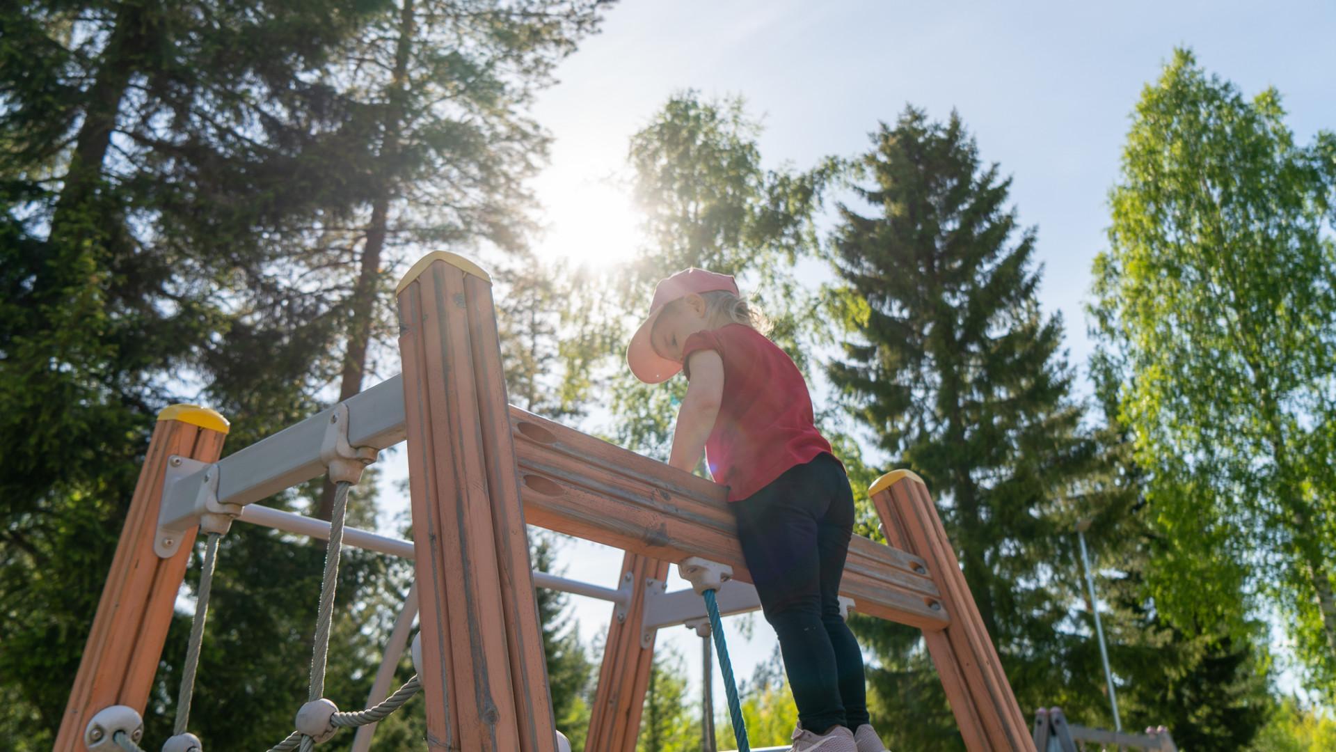Pikkutyttö kiipeilytelineessä leikkipuistossa.