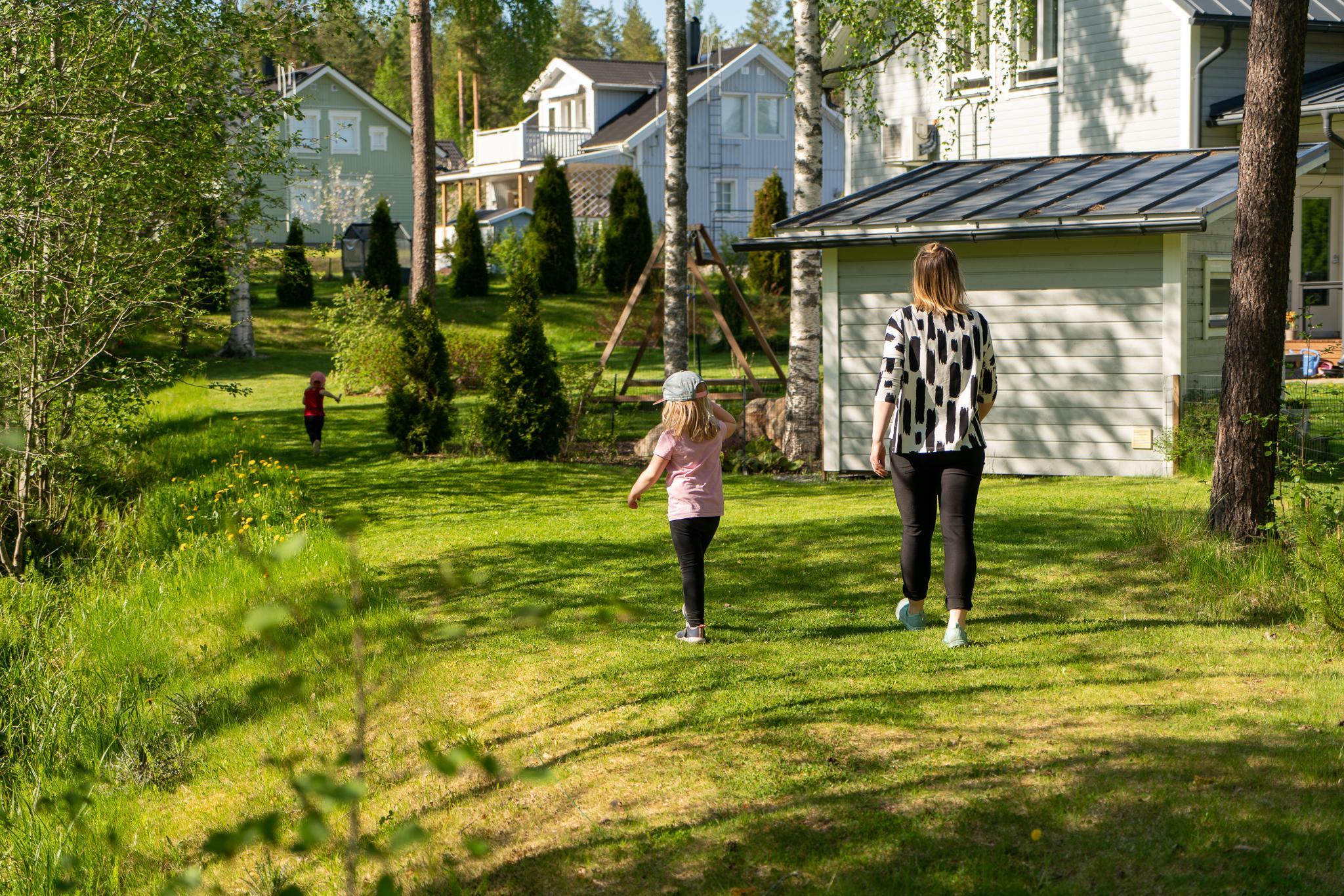 Kaisa ja tyttäret kävelevät nurmikolla omakotitalonsa takapihalla.