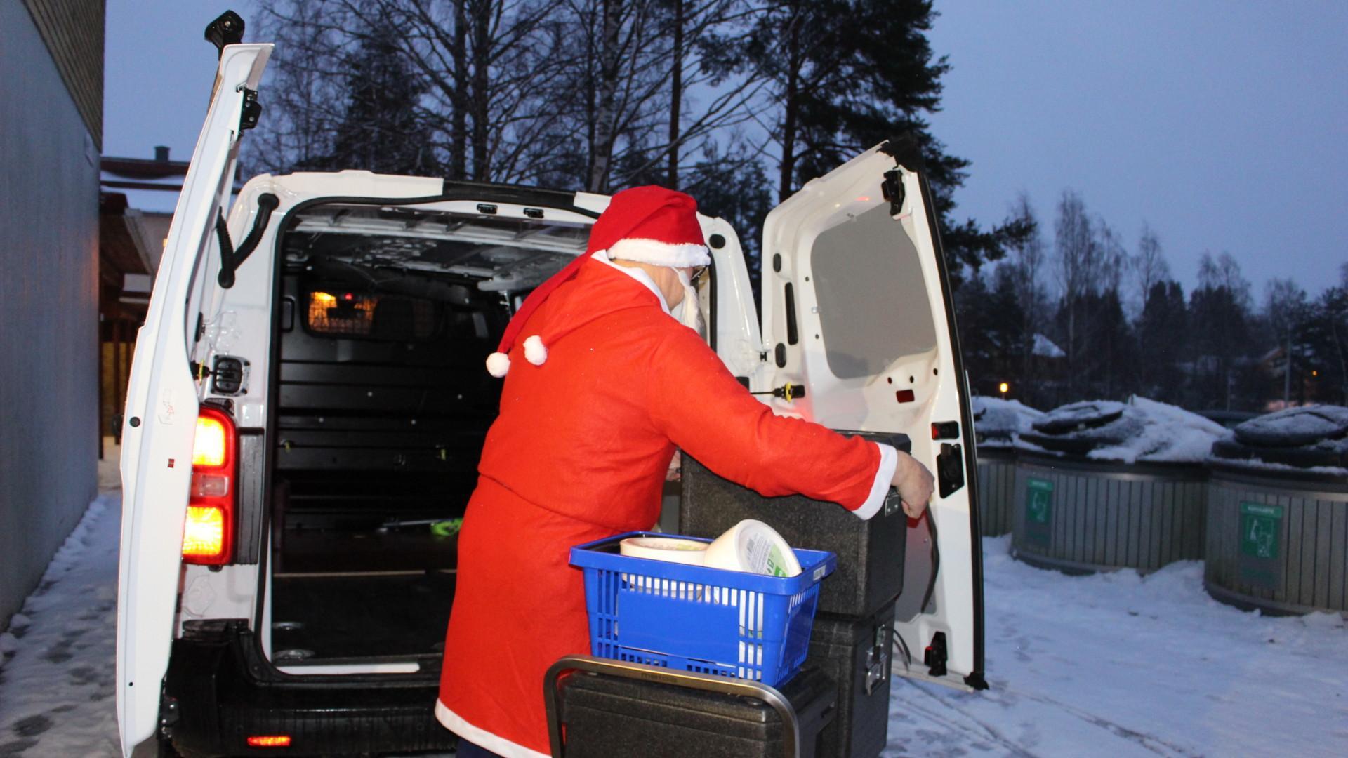 Joulupukki lastaa kyytiin joulupuuroa Oriveden yhteiskoulun keittiön ovella.