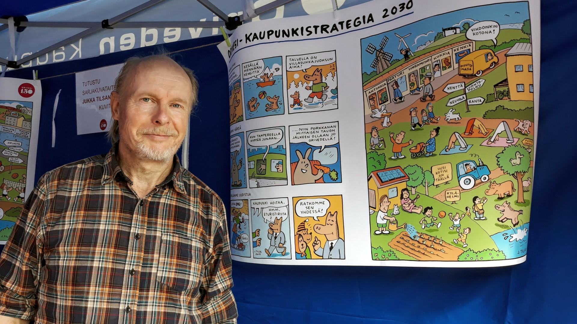 Sarjakuvataiteilija Jukka Tilsa piirtämänsä kaupunkistrategian sarjakuvakuvituksen vieressä.