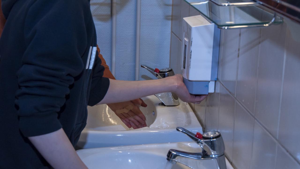 Lapset pesevät käsiä koulussa.