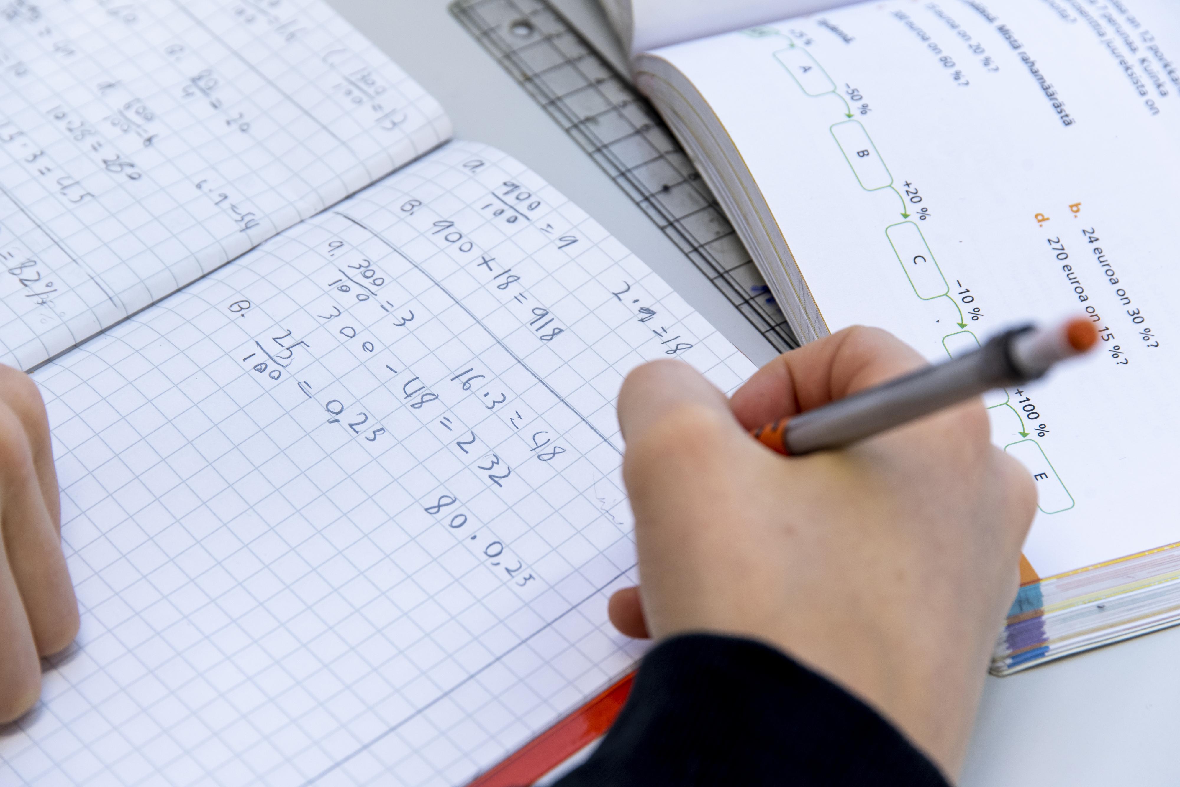 Oppilas kirjoittaa vihkoonsa oppitunnilla.