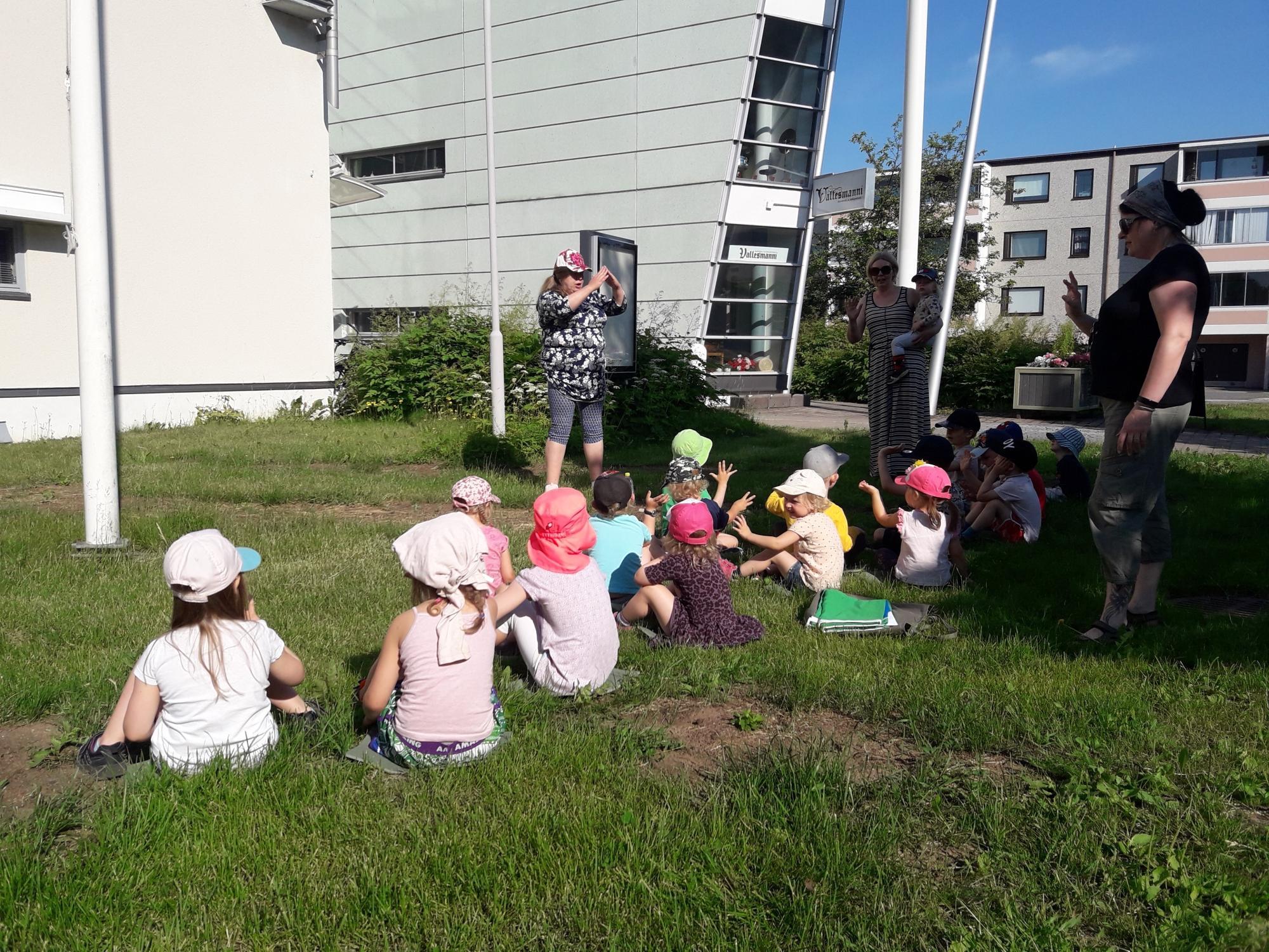 Orivarsan päiväkodin väki istuu Orivesi-talon edustalla odottamassa Vihreän lipun nostoa.