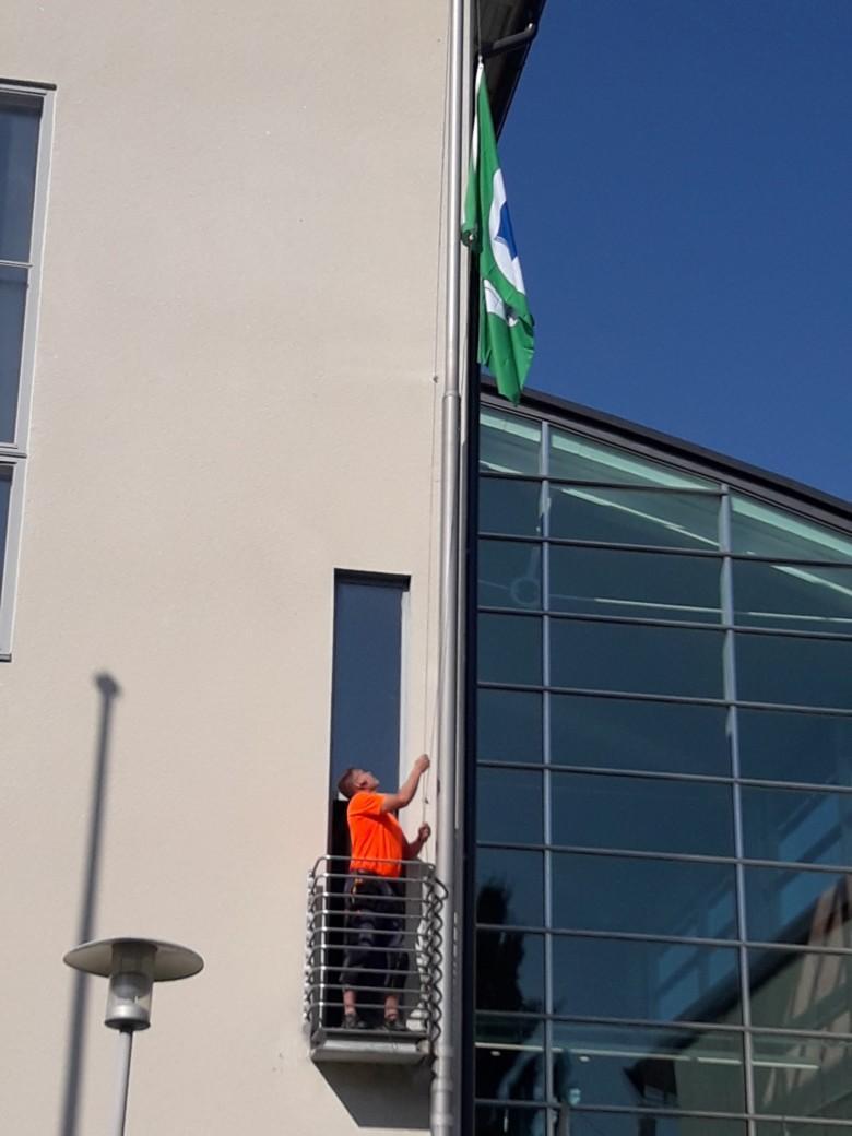 Tilapalvelun työntekijä nostaa Vihreän lipun Orivesi-talon lipputankoon.