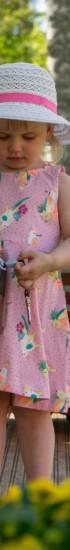 Tyttö kesäisellä pihamaalla kesämekossa ja koiran talutushihna kädessä.