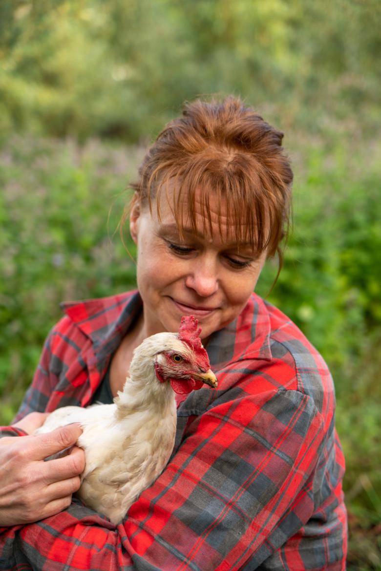Pia pitää kanaa sylissään.